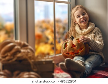 Cute little child girl looking out the window after Halloween.