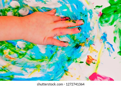 Cute little child girl painting with colorful hands and finger. Happy childhood, art concept.