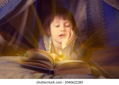 Cute little child girl reading a book in bed before going to sleep (bedtime, childhood, safety concept)