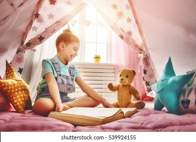 Cute little child girl is reading a book. Happy girl play at home. Funny lovely child having fun in children room.