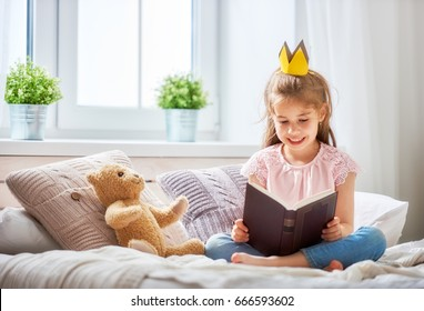 Cute little child girl reading a book in the bedroom. Kid with crown sitting on the bed near window.