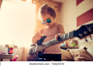 Cute little child girl in sunglasses playing guitar at home