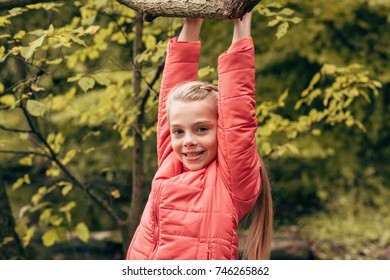 cute little child hanging on tree branch and smiling at camera