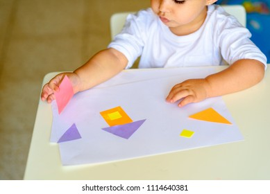 Cute little child make applique  glues colorful house, applying color paper using glue while doing arts and crafts in preschool or home. Idea for children's creativity, an art project made of paper.