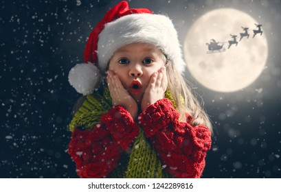 Cute little child on Christmas. Santa Claus flying in his sleigh against moon sky. Happy kid enjoy the holiday. Portrait of girl with gifts on dark background.