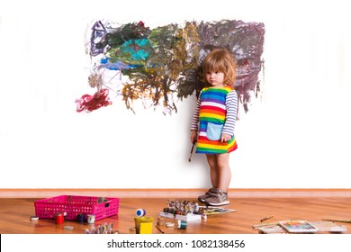 cute little child painting  on wall in room