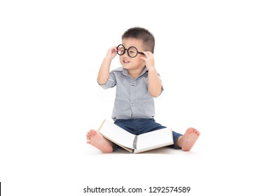 Cute little child play with book and wearing glasses while sitting on floor isolated over white background, Asian baby boy and education concept