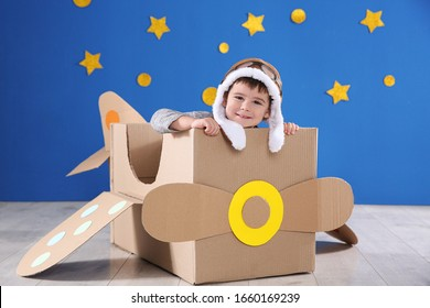 Cute little child playing with cardboard airplane near blue wall