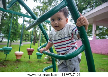 ef9d7a35a cute little child playing at kid play ground looking at camera andvclimbing  up iron stairs