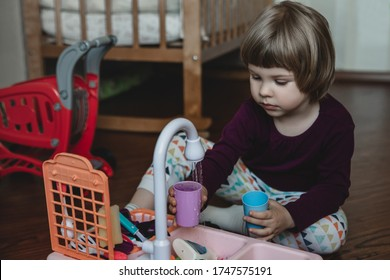 Cute little child plays kid's kitchen. Toy dishwasher. Kid's Hobby concept.
