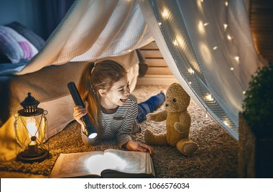 Cute little child is reading a book with flashlights in tent. Happy girl playing at home. Funny lovely kid having fun in room.