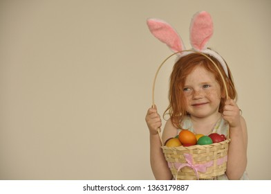 Cute little child with red hair wearing bunny ears on Easter day. Girl holding basket with painted eggs.