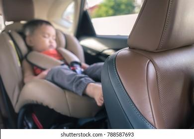 cute little child sleeping on a car seat in a car