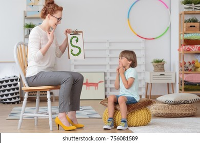 Cute little child with speech impediment and smiling young preschool teacher learning the alphabet letters in kindergarten classroom
