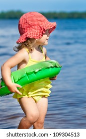 Cute little child standing on beach with swimming ring