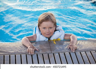 Cute little child swimming with life jacket in outdoor pool