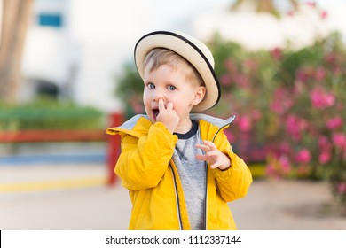 Cute little child or toddler boy picking his nose outdoors on summer.