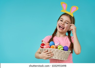 Cute little child wearing bunny ears on Easter day. Girl holding basket with painted eggs on light blue background.