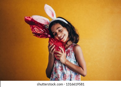 Cute little child wearing bunny ears on Easter day on color background. Girl holding chocolate easter egg