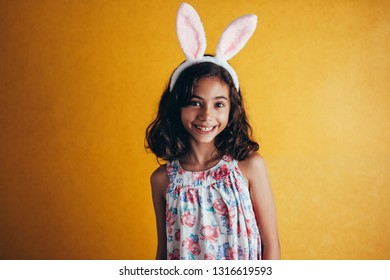 Cute little child wearing bunny ears on Easter day on color background
