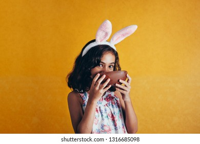 Cute little child wearing bunny ears on Easter day on color background. Girl eating chocolate easter egg