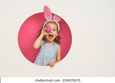 Cute little child wearing bunny ears on Easter day. Girl with painted eggs on pink and white background.