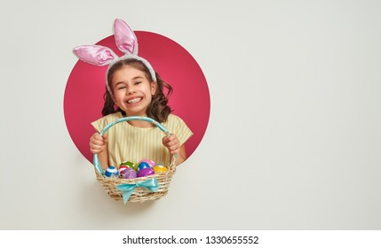 Cute little child wearing bunny ears on Easter day. Girl with painted eggs on white and pink background.