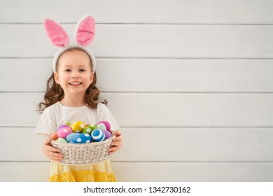 Cute little child wearing bunny ears on Easter day. Girl holding basket with painted eggs.