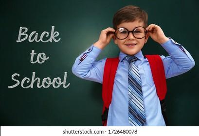 Cute little child wearing glasses near chalkboard with phrase BACK TO SCHOOL
