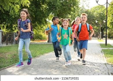 Cute little children with backpacks running outdoors. Elementary school
