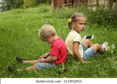 Cute little children, boy and girl, brother and sister, sitting back to back and sharing a photo on social media in internet