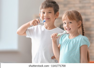 Cute little children brushing teeth at home