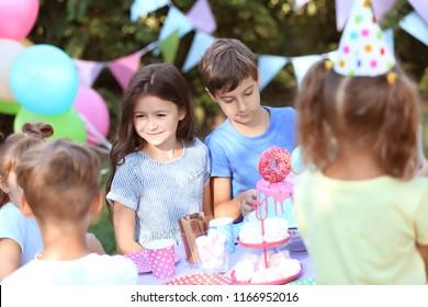 Cute little children celebrating Birthday outdoors