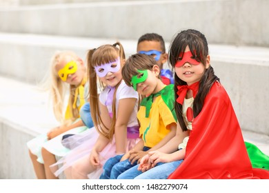 Cute little children dressed as superheroes sitting on stairs outdoors