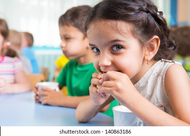 Cute little children drinking milk at daycare
