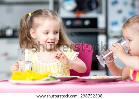 Cute little children drinking water at daycare or nursery