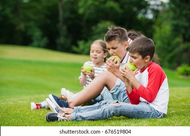 Cute little children eating green apples while resting in park