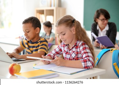 Cute little children with gadgets sitting at desk in classroom. Elementary school