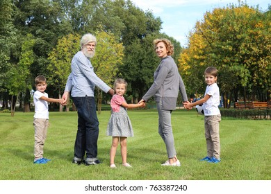Cute little children with grandparents in park on sunny day