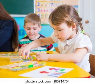 Cute little children having applique lesson at kindergarten