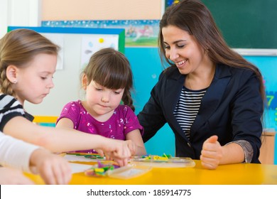 Cute little children having applique lesson at kindergarten
