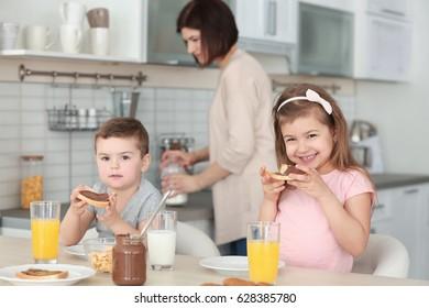 Cute little children having breakfast at home