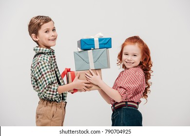 cute little children holding gift boxes and smiling at camera isolated on grey