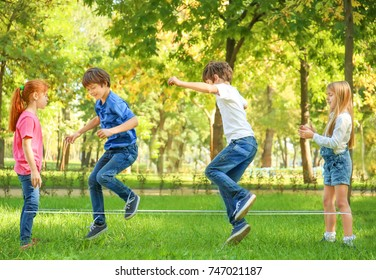 Cute little children jumping rope in park