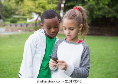Cute little children looking at smartphone in the park