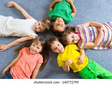 Cute little children lying on floor in kindergarten