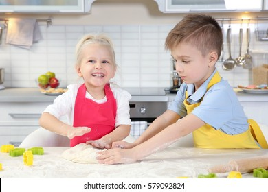 Cute little children making Easter cookies at kitchen