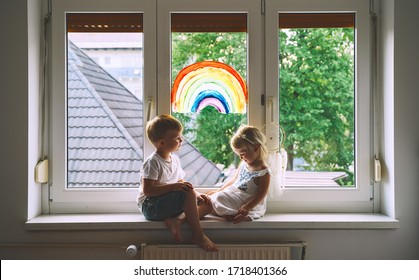 Cute little children on background of painting rainbow on window. Photo of kids leisure at home, safety joy symbol, happy childhood. Positive visual support during quarantine. Family Art Background