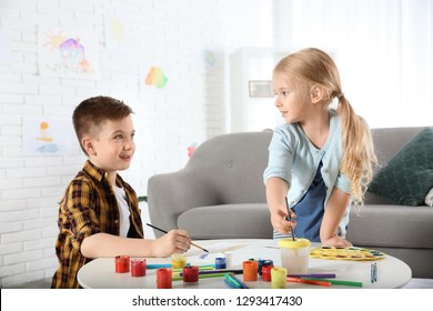 Cute little children painting together at home