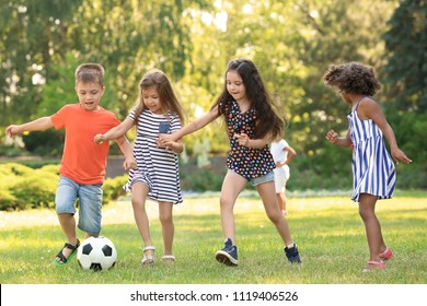 Cute little children playing football outdoors